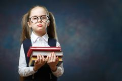 Serious Schoolgirl Wear Glasses Hold Pile of Book royalty free stock photography