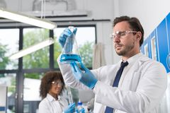 Serious Scientist Looking At Flask With Blue Liquid In Laboratory Over Group Of Scientific Researchers Making Stock Images