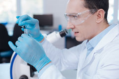 Serious scientist posing with opened mouth. Profile photo. Delighted male person wearing protective glasses sitting in semi position while looking attentively at Stock Photography