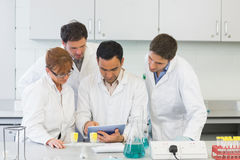 Serious scientists using tablet PC in the lab Stock Photos