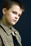 Serious scout boy portrait. Portrait of a teenage scout boy wearing a greenish uniform. Serious expression on his face Stock Photos