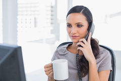 Serious secretary answering phone Stock Photos