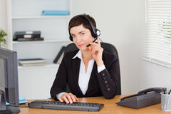 Serious secretary calling with a headset Stock Photography