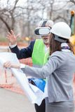 Serious senior architect or businessman using virtual reality goggles to visualize construction project on a construction site. Young female engineer holding stock photography