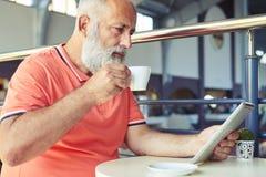 Serious senior bearded man drinking coffee Royalty Free Stock Photography
