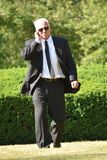 Serious Senior Bodyguard Wearing Sunglasses Walking. A retired senior adult male stock photos