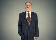 Serious senior businessman on gray wall background Royalty Free Stock Photos