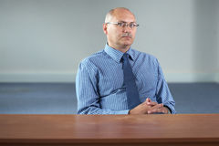 Serious senior businessman sits behind empty desk Stock Photos