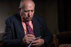 Serious Senior Businessman Taking Down Notes Stock Image