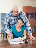 Serious senior couple fills in questionnaire Stock Photos
