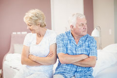 Serious senior couple sitting on bed at home Stock Photos