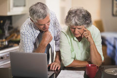 Serious senior cpouple reading documents by laptop on table Royalty Free Stock Image