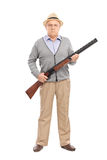 Serious senior gentleman holding a shotgun. Full length portrait of a serious senior gentleman holding a shotgun and looking at the camera isolated on white Royalty Free Stock Photos