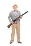 Serious senior gentleman holding a shotgun Royalty Free Stock Photos