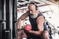 Serious senior male is enjoying sporty lifestyle. Music helps. Concentrated old bearded man is sitting on bench and doing exercises with dumbbell while listening Stock Photo