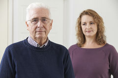 Serious Senior Man With Adult Daughter At Home. Serious Senior Man With Concerned Adult Daughter At Home Stock Photography