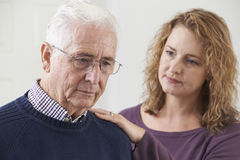 Serious Senior Man With Adult Daughter At Home Stock Photography