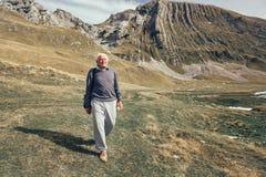 Serious senior man on the mountains road. Serious senior man with gray hair on the mountains road Royalty Free Stock Photos