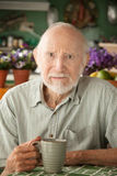 Serious senior man with mug Stock Photography