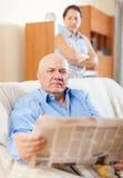 Serious senior man reading newspaper Royalty Free Stock Photo