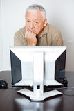 Serious Senior Man Sitting At Computer Desk In Class Royalty Free Stock Image