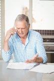 Serious senior man talking on mobile phone Stock Images