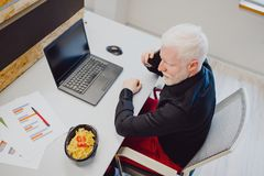 Serious Senior Man Talking On The Phone In The Office Royalty Free Stock Photography