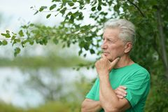 Serious senior man. Thinking in park on green background Stock Images