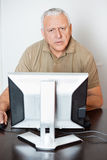 Serious Senior Man Using Computer At Desk In Class Stock Photo