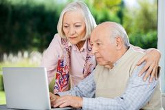Serious Senior Man And Woman Using Laptop Stock Images