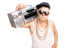 Serious senior rapper holding a ghetto blaster. Over his shoulder and looking at the camera isolated on white background Royalty Free Stock Photo