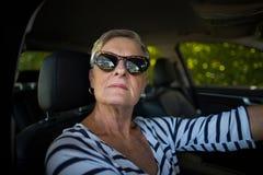Serious senior woman driving car. Portrait of serious senior woman driving car Stock Photos