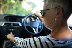Serious senior woman driving car. Rear view of serious senior woman driving car Stock Images
