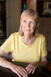 Serious senior woman seated at table Royalty Free Stock Photography