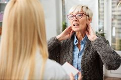 Serious senior woman with neck pain or thyroid problems consulting with doctor stock photo