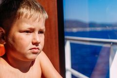 Serious seven-year-old boy looks out the window on the ship stock photos