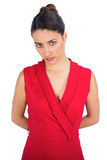 Serious sexy brunette in red dress posing Royalty Free Stock Photography