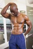 Serious shirtless muscular man posing in gym Stock Images