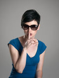 Serious short hair brunette wearing sunglasses with finger on her lips hush gesture Stock Photo