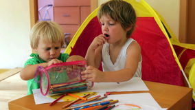 Serious siblings playing with pencils. In home stock footage