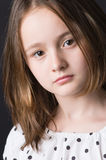 Serious sight. The girl of ten years in a white dress on a black background Royalty Free Stock Photos