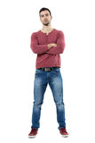 Serious skeptical young man with crossed arms looking at camera Stock Photo