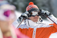 Serious skier adjusting goggles Stock Photo