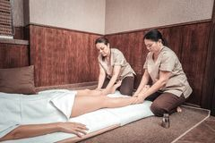 Serious skilled women performing massage for legs. Special therapy. Serious skilled women sitting on the floor while performing massage for legs stock image
