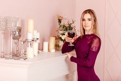A serious slender twenty-year-old woman stands by the fireplace and holds a glass of red wine in her hand. Woman and alcohol royalty free stock photo