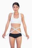 Serious slim woman measuring her waist Stock Images