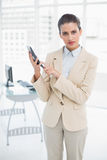 Serious smart brown haired businesswoman using a calculator Royalty Free Stock Images