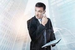 Serious smart businessman holding a pen Stock Image