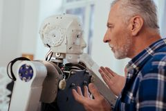 Serious smart engineer looking at the robot. Progressive technology. Serious smart engineer looking at the robot while standing in front of him Royalty Free Stock Photos