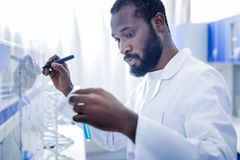 Serious smart man developing a formula. Genius chemist. Serious nice smart man standing in front of the whiteboard and developing a formula while working in the Stock Photo